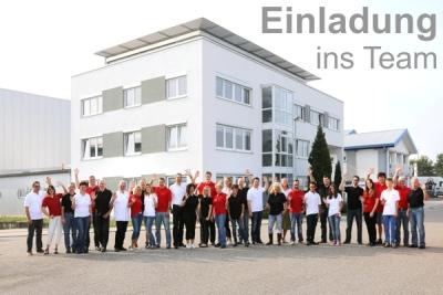 Die ca. 45 Mitarbeiter der Michael Koch GmbH stehen winkend vor der Michael Koch GmbH und begrüßen den neuen Mitarbeiter.